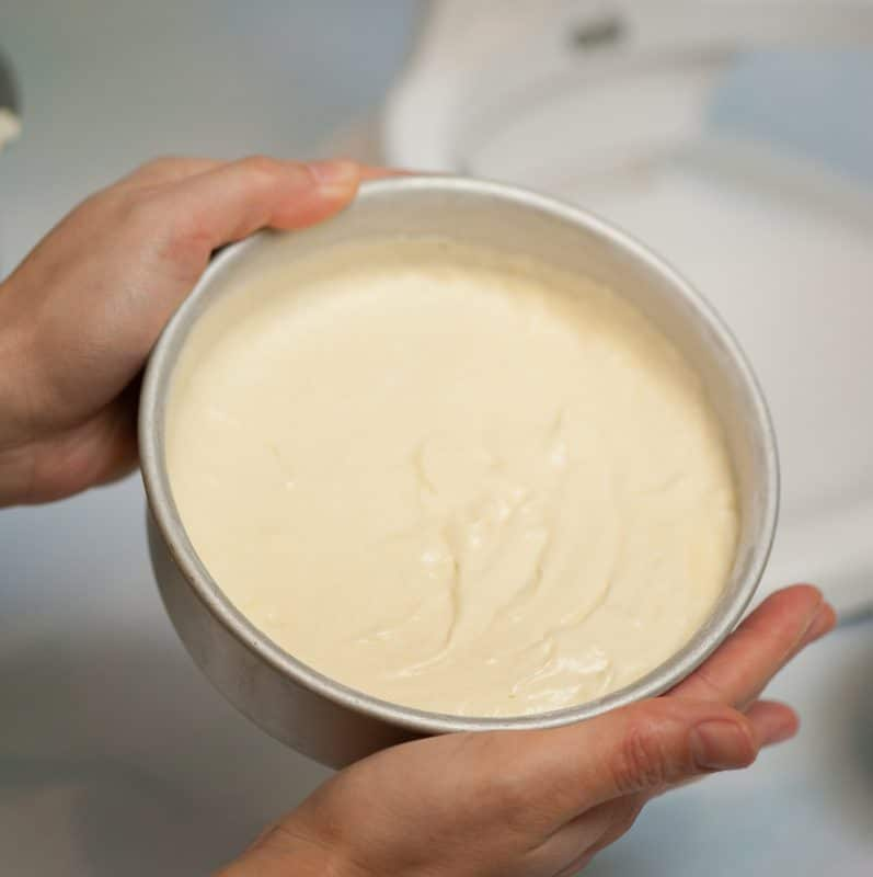 grease the cake pans with vegetable oil then dust with cake flour and tap out the excess then fill three quarters full with cake batter