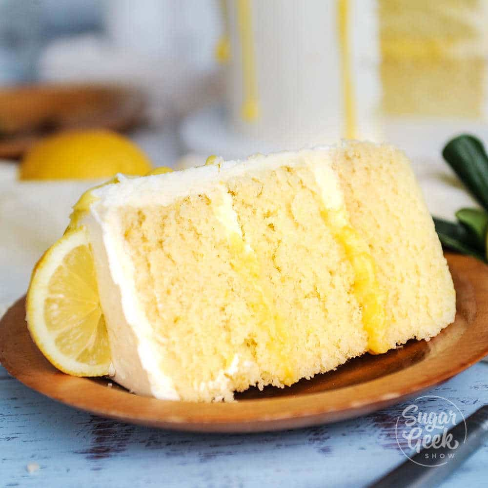 slice of moist lemon cake with lemon curd and easy buttercream frosting on a wooden plate
