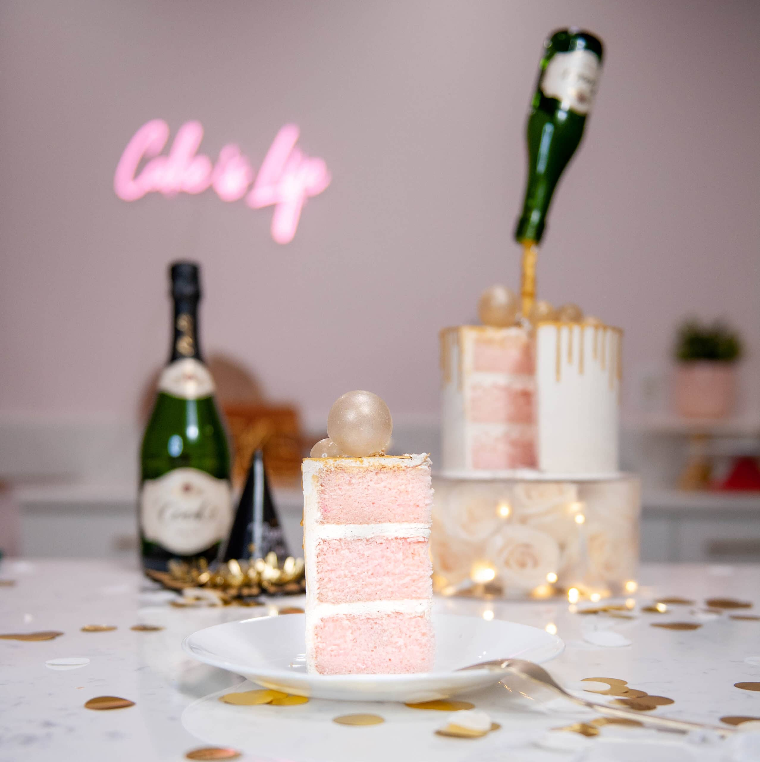 champagne cake on a plate with cake and champagne bottle in the background