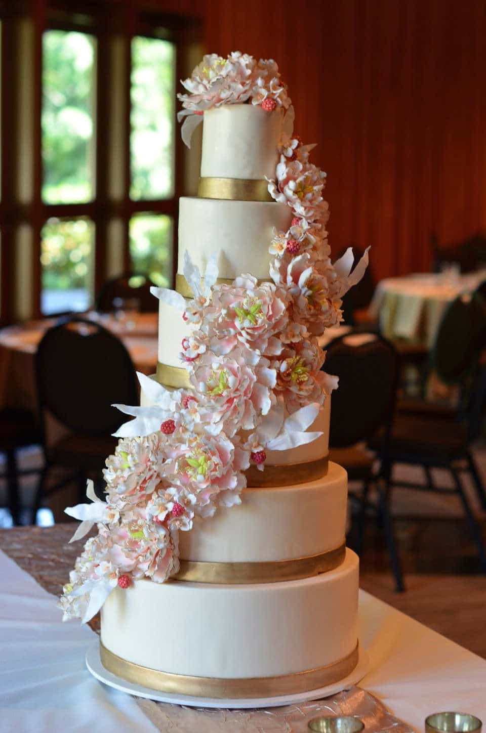 6 tier wedding cake with gold bands and gumpaste peony