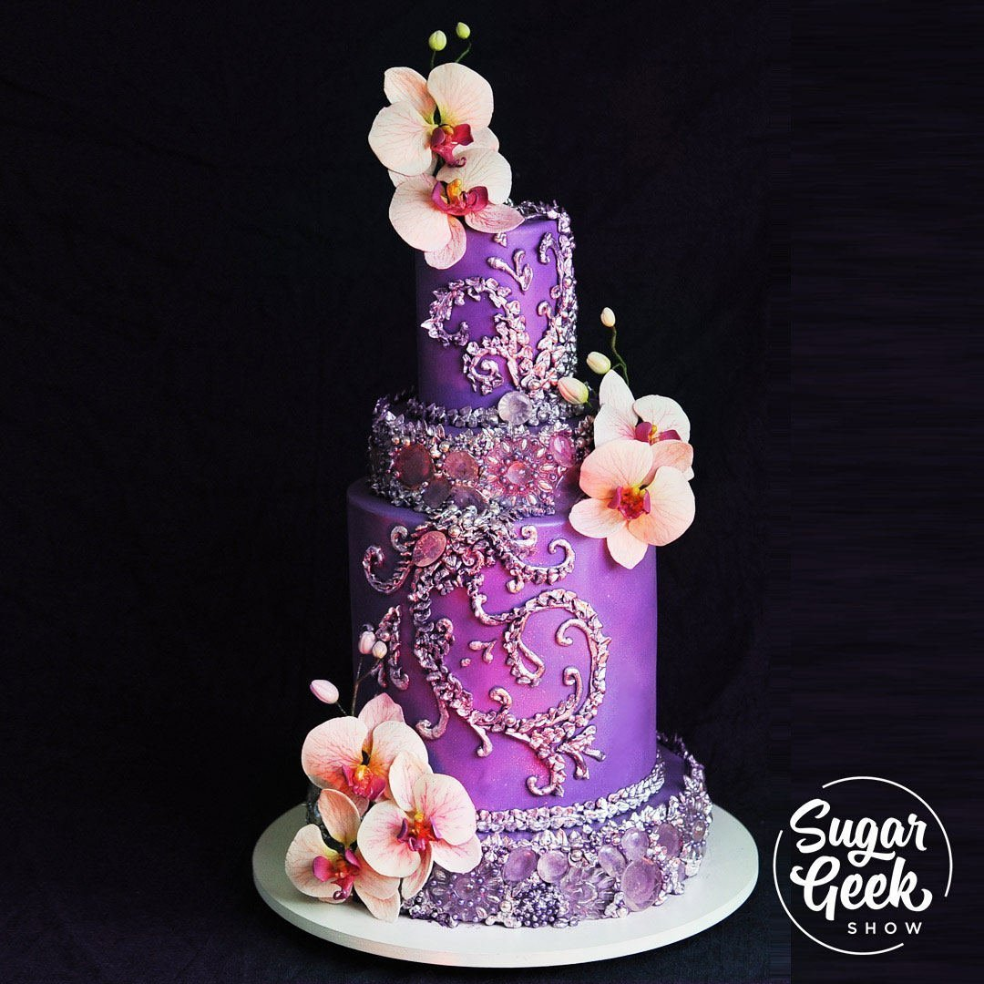 This is a re-make of one of my very early cakes in my career. Since then, it has been pinned, shared and re-posted thousands of times.  I have always had a thing for shiny edible bling on cakes and get many requests on how to re-create these edible jewels. So here it is! How to make the purple bling cake complete with edible jewels and silver piping and gorgeous, life-like gumpaste orchids!