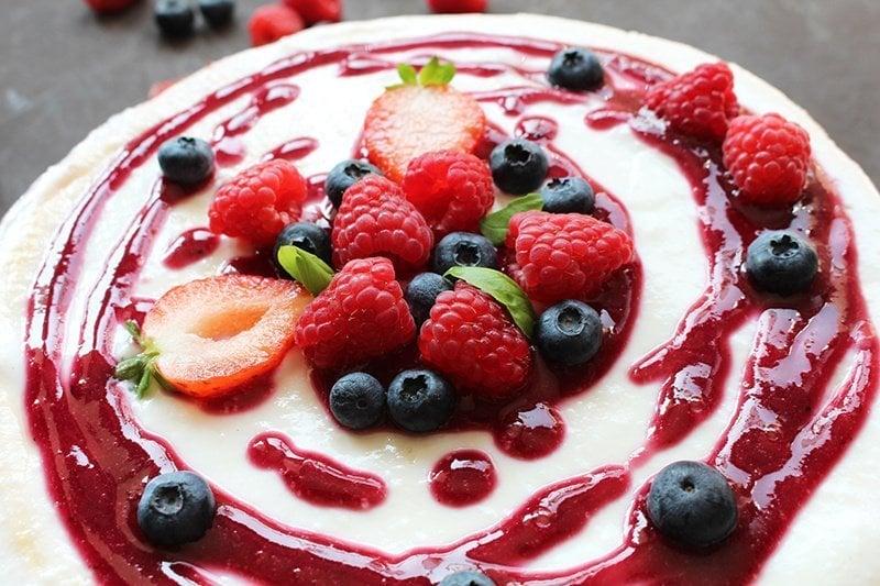 strawberry puree on cheesecake with fresh berries