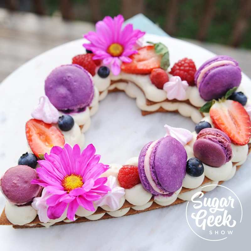 cream tart in the shape of a heart topped with fresh flowers, fruit and macarons