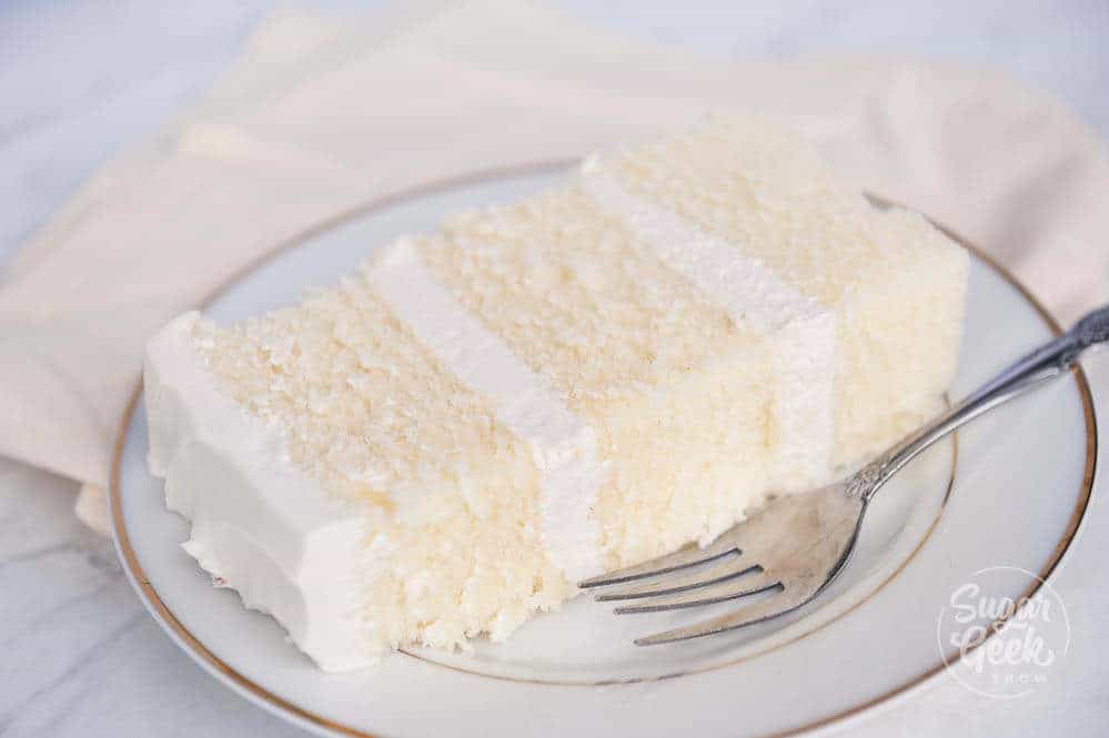 slice of white velvet cake with ermine frosting on a plate with a silver fork