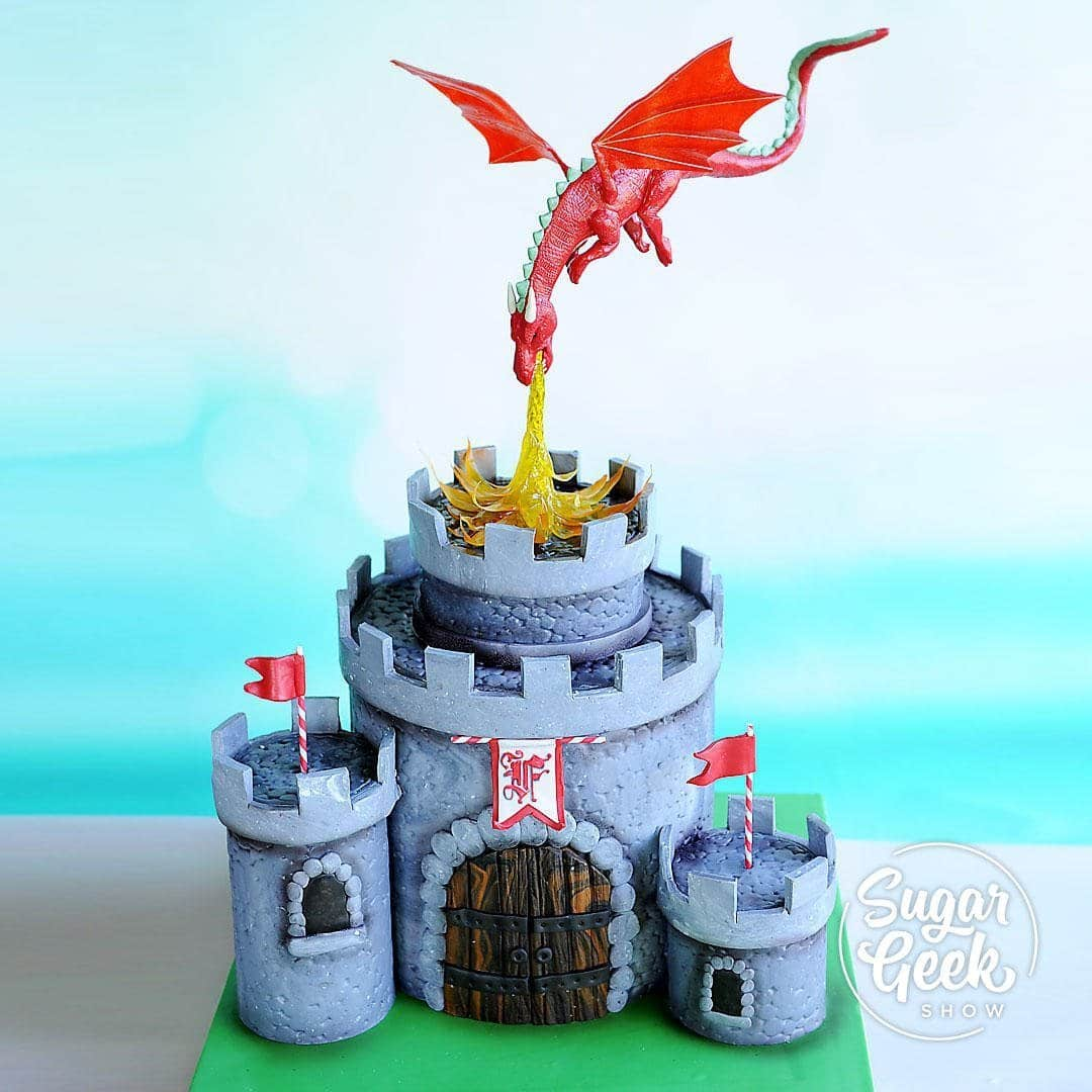Birthday cakes are one of my favorite things to make and this castle cake with a dragon cake topper is the perfect sort of cake to make for the little king or queen's birthday.  Learn how to make a dragon cake topper with posable wings, isomalt dragon fire, all the little details on the castle, how to hand-letter fancy monograms and more!
