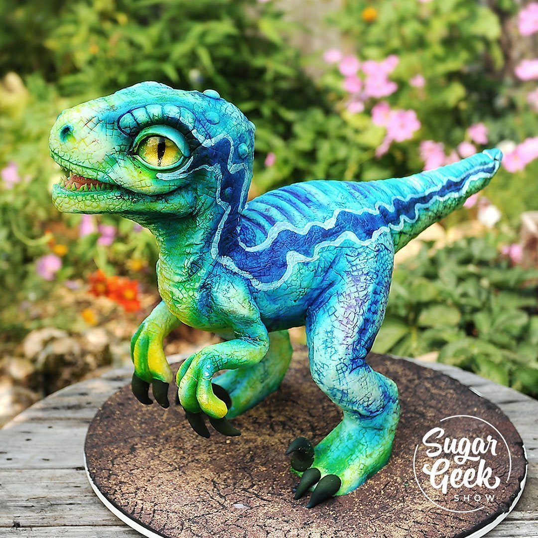 Avalon's Dino-FOUR birthday was this past week and I wanted to create a big showpiece cake for her birthday along with a baby dinosaur cake and this was the result! Learn to make a cutesy blue raptor showpiece out of rice cereal treats or cake, sparkling dinosaur eyes, how to scale photo references to create any cake you want and how to make a cake structure to match.