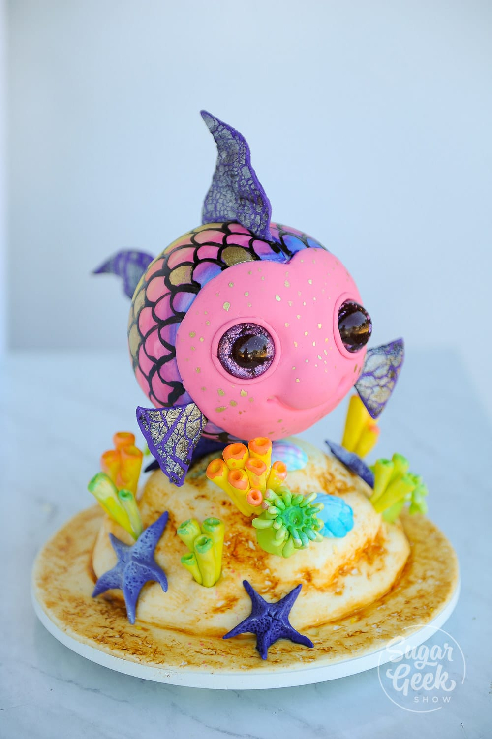 rainbow fish tutorial with a simple cake structure, glitter eyes, crackled fondant and fun watercolor scales