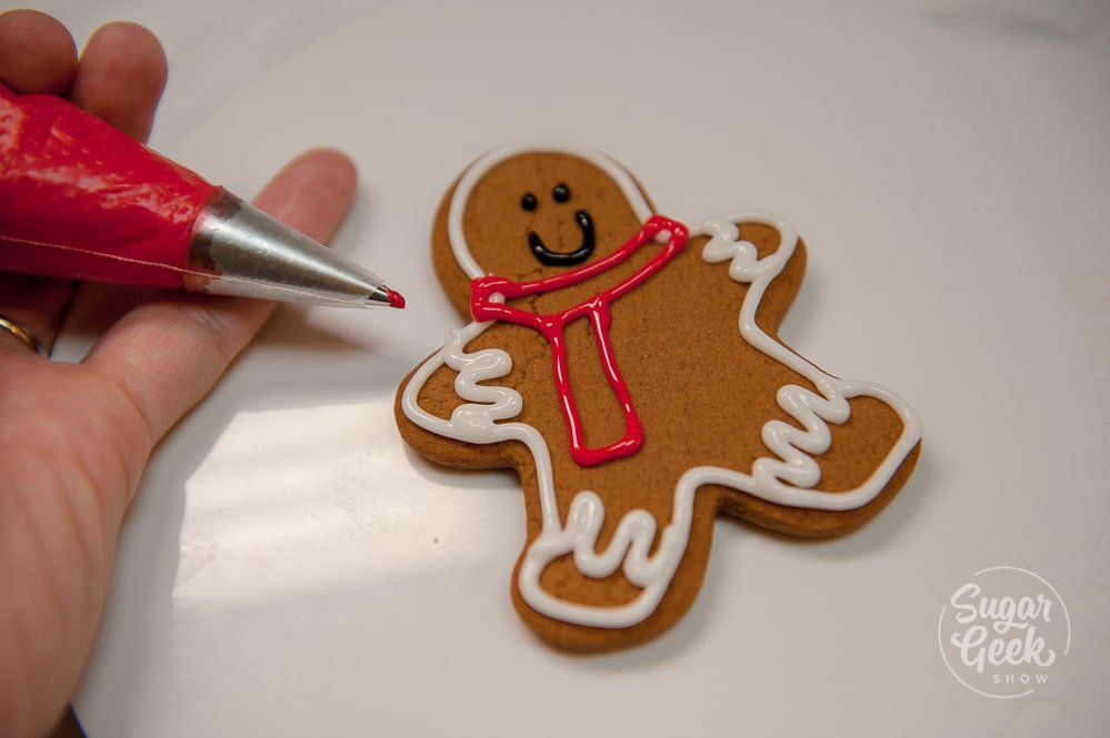 Outline a scarf for the gingerbread man in red royal icing