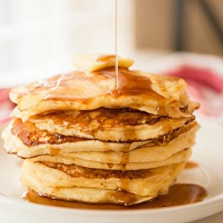 stack of brown butter buttermilk pancakes with syrup being drizzled on top