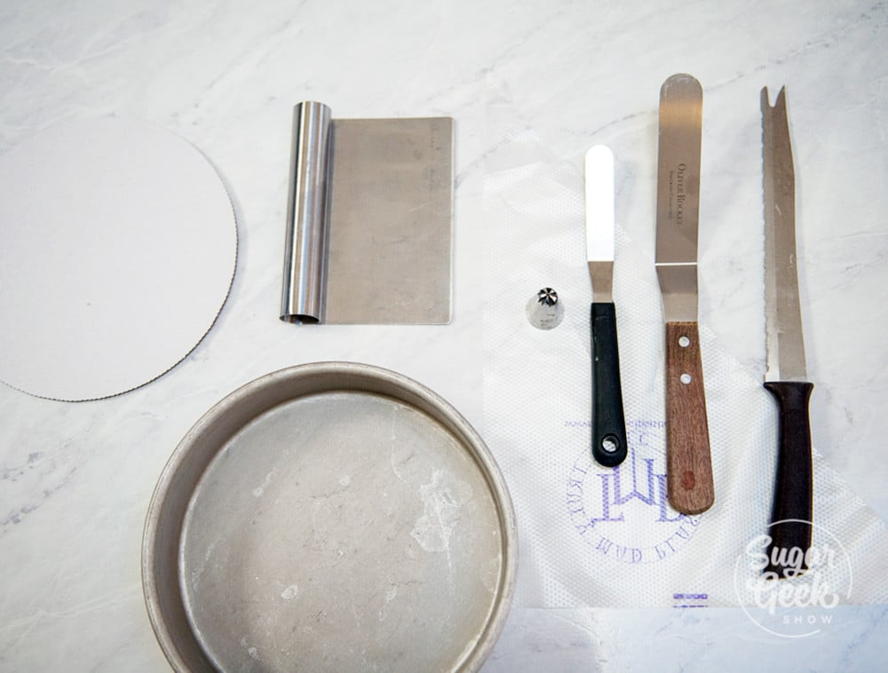 cake cardboard, cake pan, bench scraper, piping tip, piping bag, small and large offset spatula and serrated knife