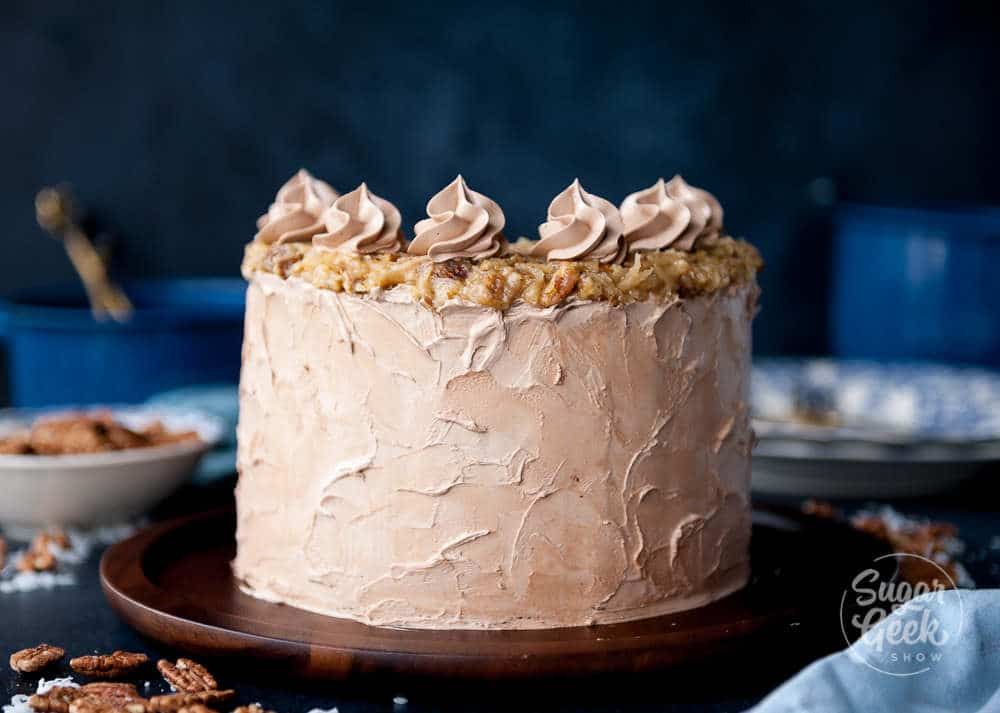 close up of german chocolate cake frosted with chocolate swiss meringue buttercream and coconut pecan frosting
