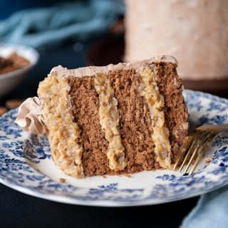 close up of german chocolate cake on a blue patterned plate with cake in the background