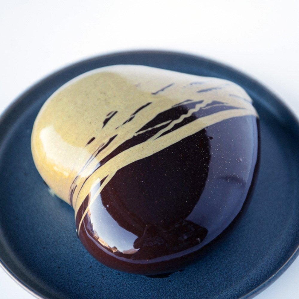 chocolate mirror glaze cake with gold drizzle on a black plate