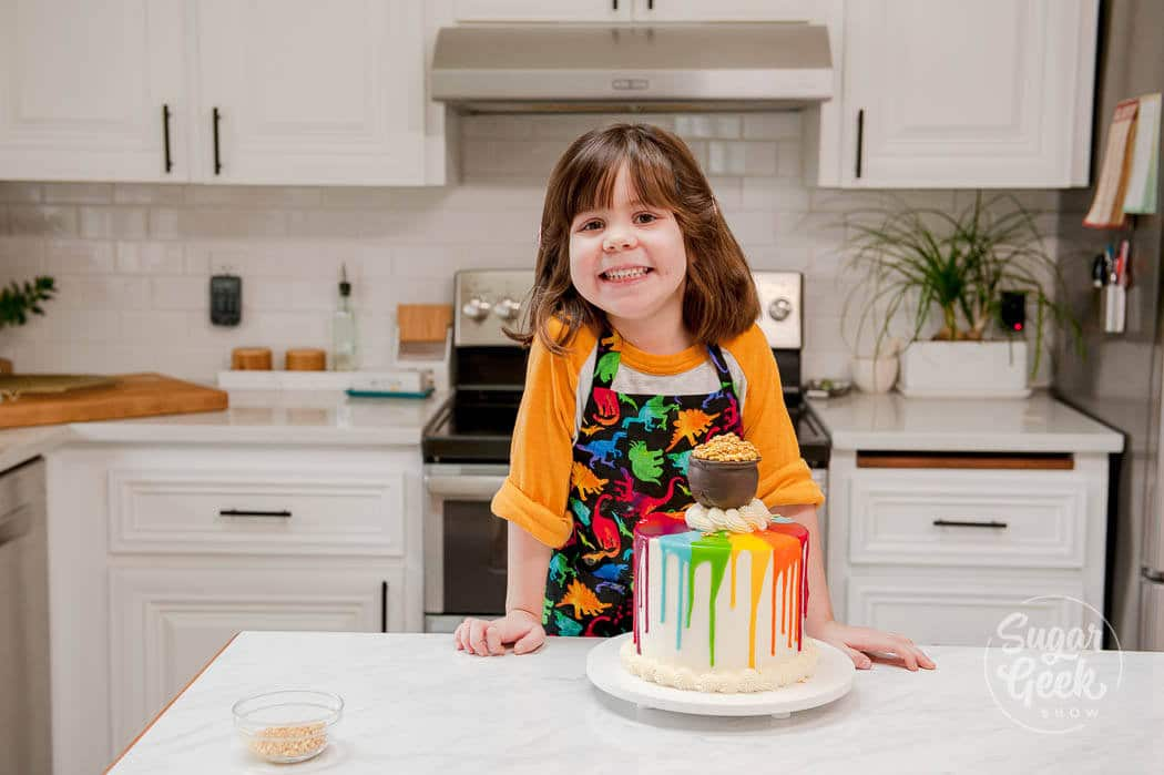 kid baking rainbow drip pot of gold cake for saint patricks day
