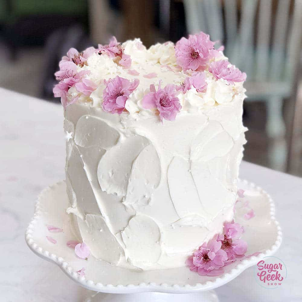 vanilla cake frosted with rustic buttercream and decorated with fresh cherry blossoms