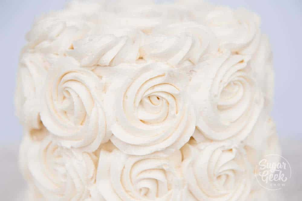 ermine frosting piped into rosettes on a cake