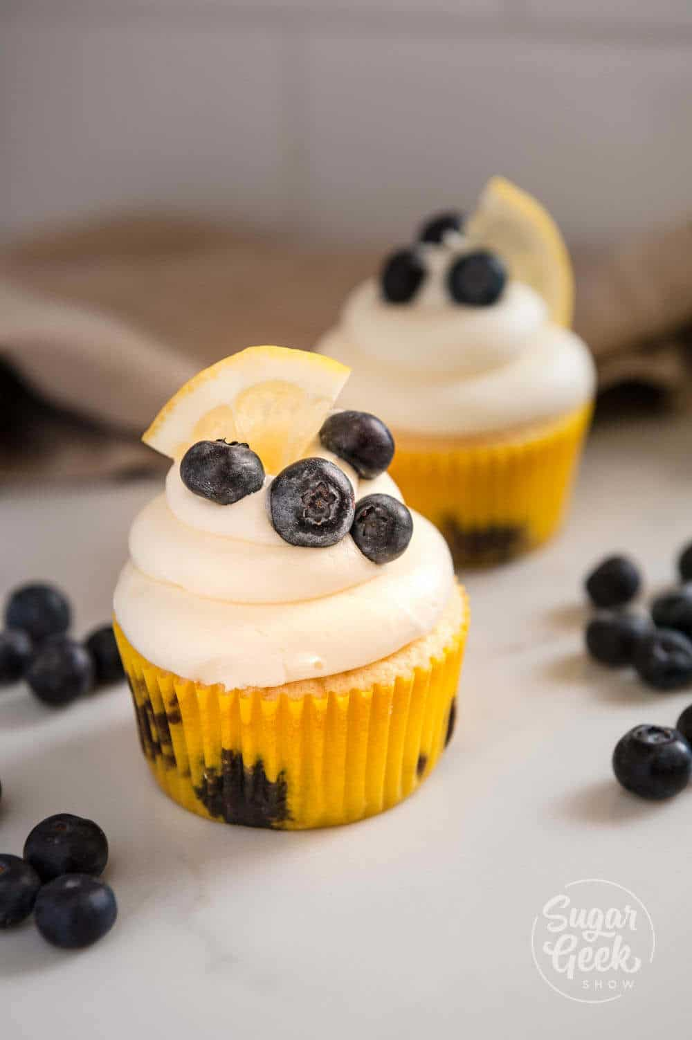 lemon blueberry cupcakes with cream cheese frosting and topped with fresh blueberries and a lemon slice