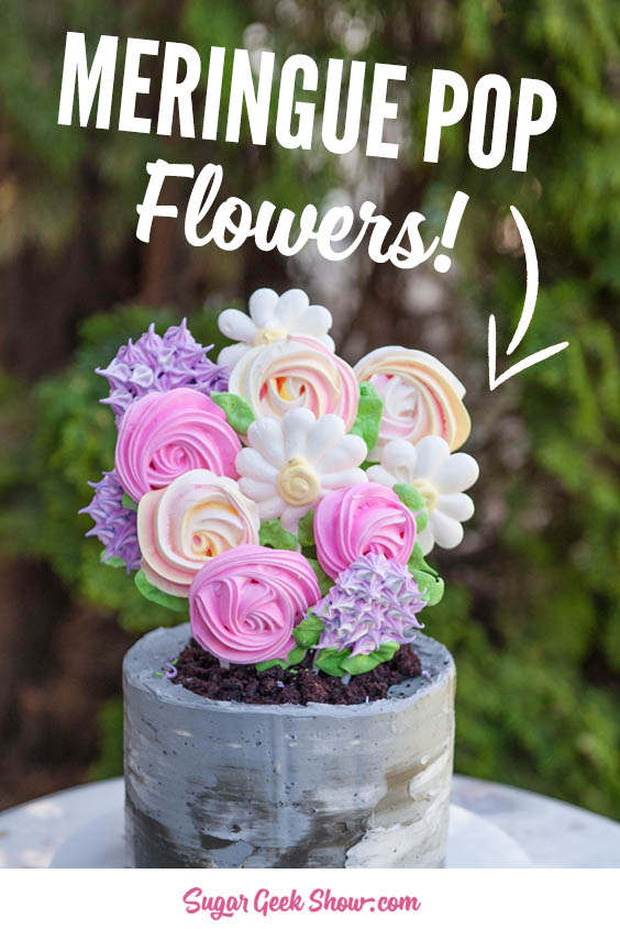 Meringue pop flowers on chocolate cake covered in buttercream that looks like a concrete texture