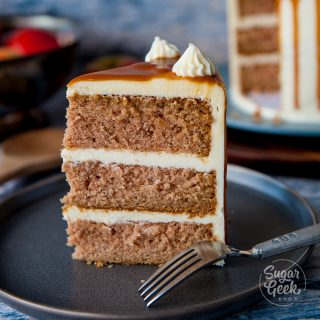 slice of applesauce cake with cream cheese frosting on black plate