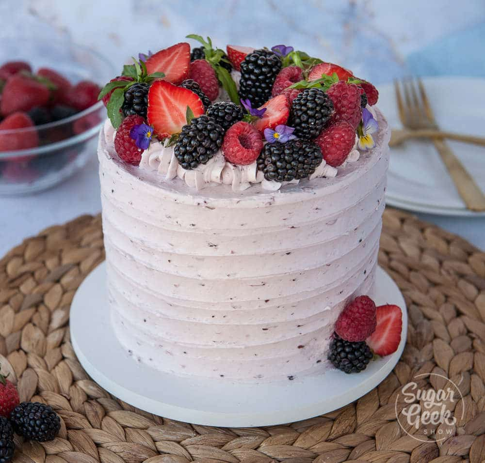 berry cake with berry buttercream and fresh berries on top