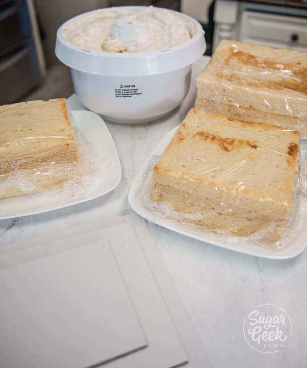 square cakes wrapped in plastic wrap with bowl of buttercream in background