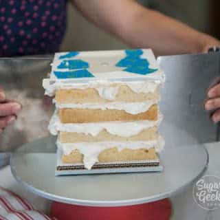 Use bench scrapers to make sure acrylics are lined up and apply a thin layer of buttercream for the crumbcoat