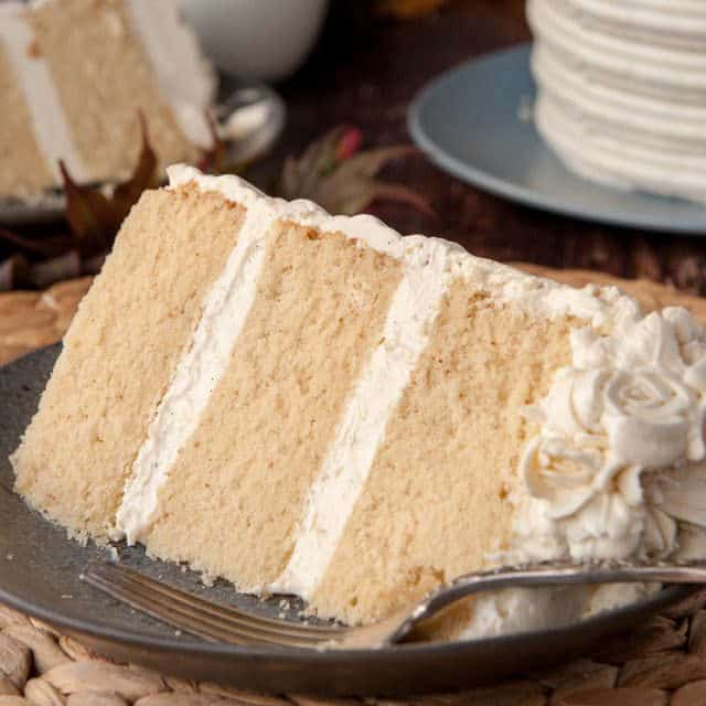 slice of brown butter cake with vanilla bean buttercream on a black plate