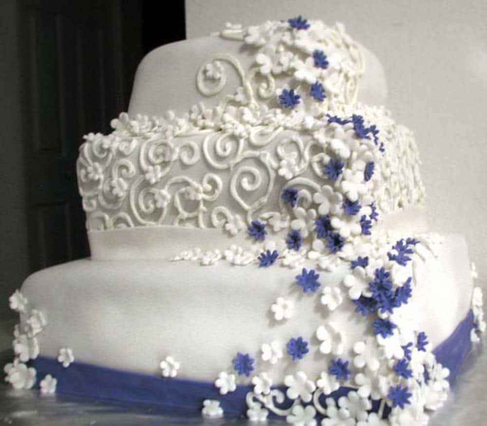 Three tier white wedding cake with crooked sides and corners. Bad piping and ugly fondant flowers