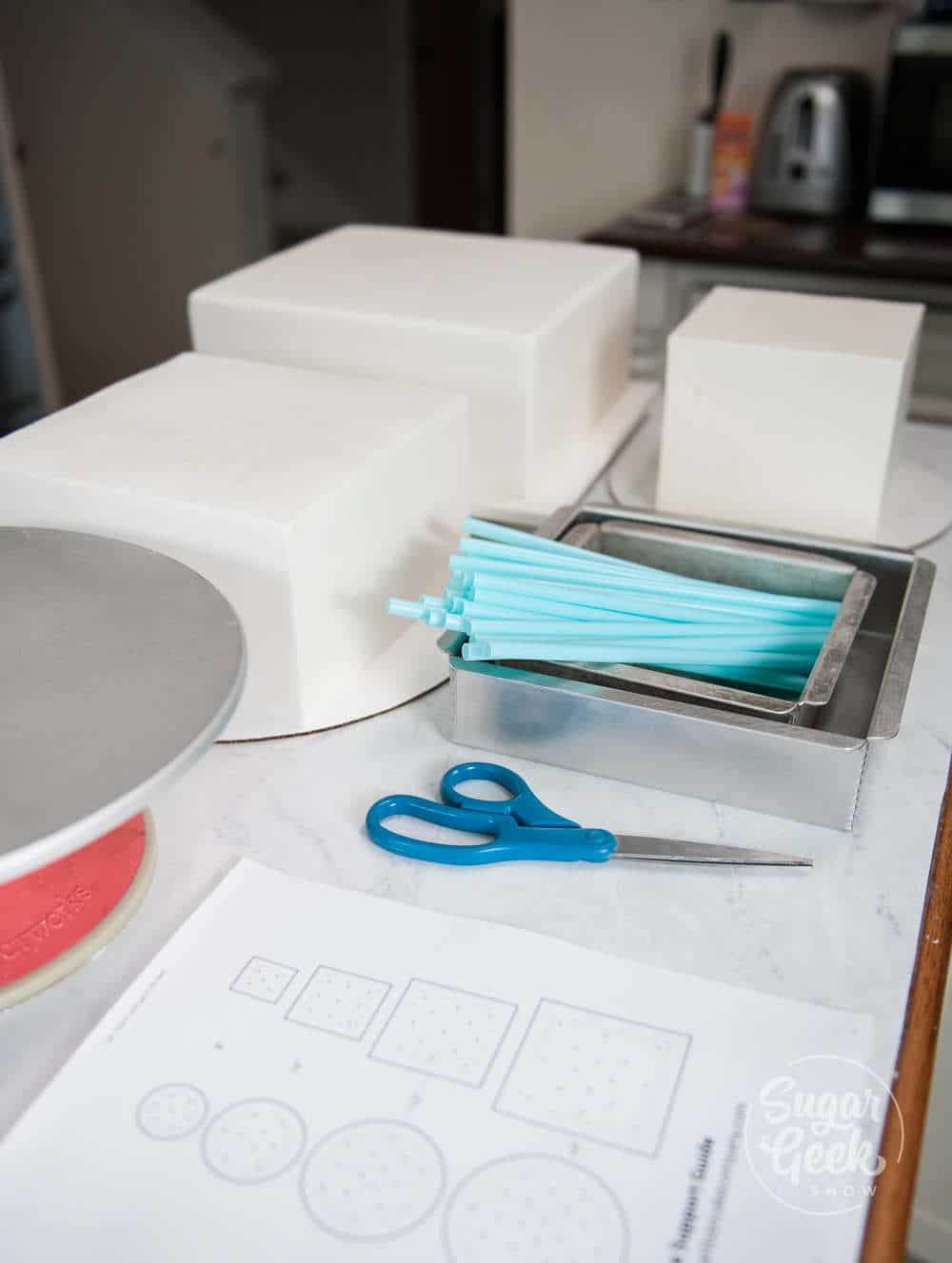 wedding cake supplies - turntable, thick milkshake straws, straw guide, scissors, square cake pans, three tiers of frosted and fondant covered cake