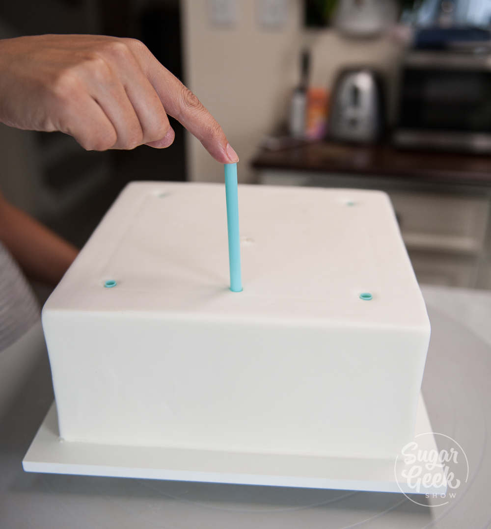 inserting thick milkshake straws into a chilled cake using the straw guide