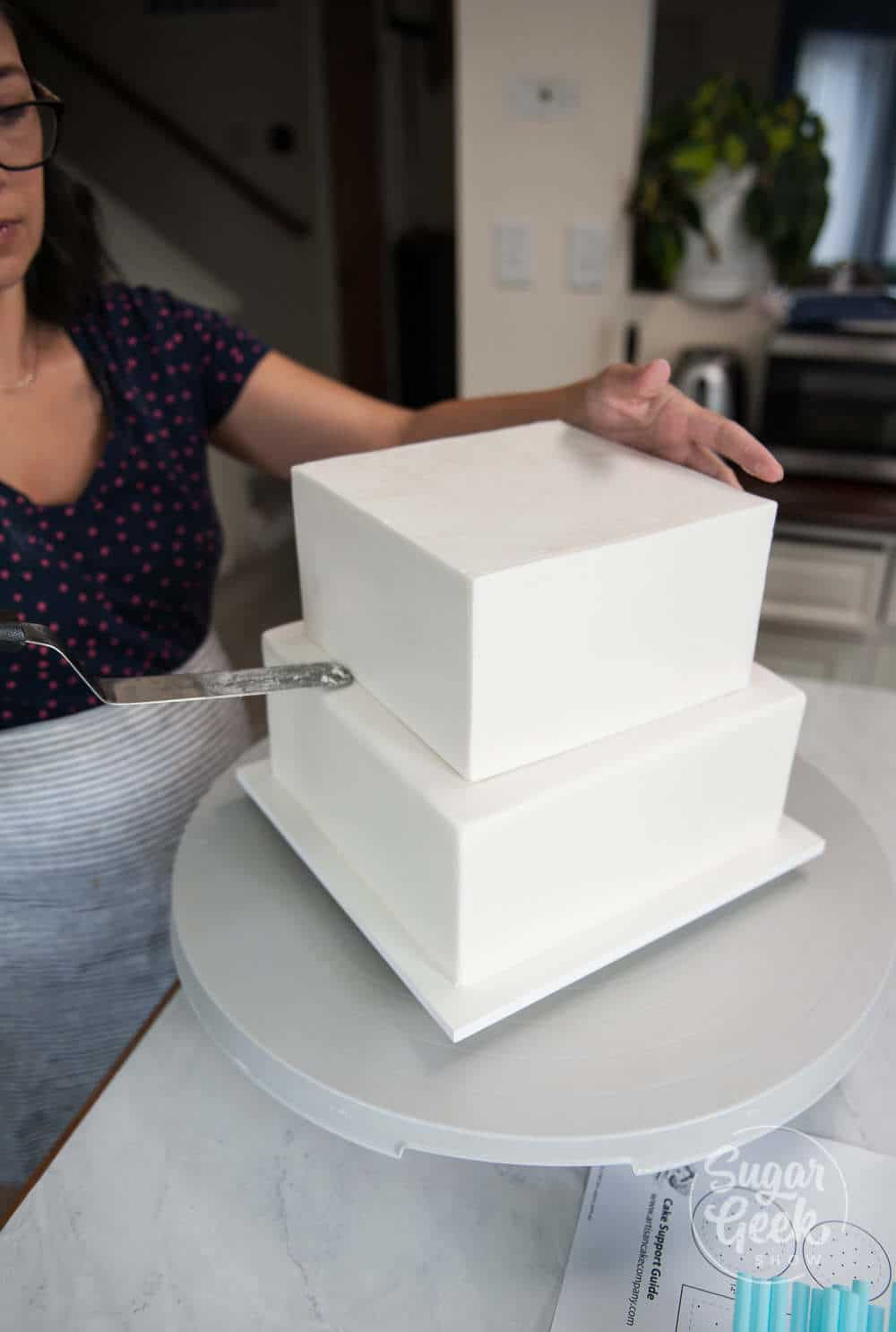 assembling the chilled wedding cake tiers using an offset spatula