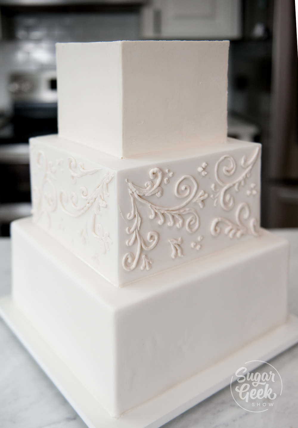 Three tier square buttercream wedding cake with white scrollwork on the center tier