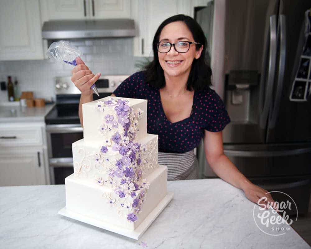 liz marek smiling at the camera in her kitchen holding a piping bag standing behind three tier square white wedding cake with purple buttercream flowers flowing down the front