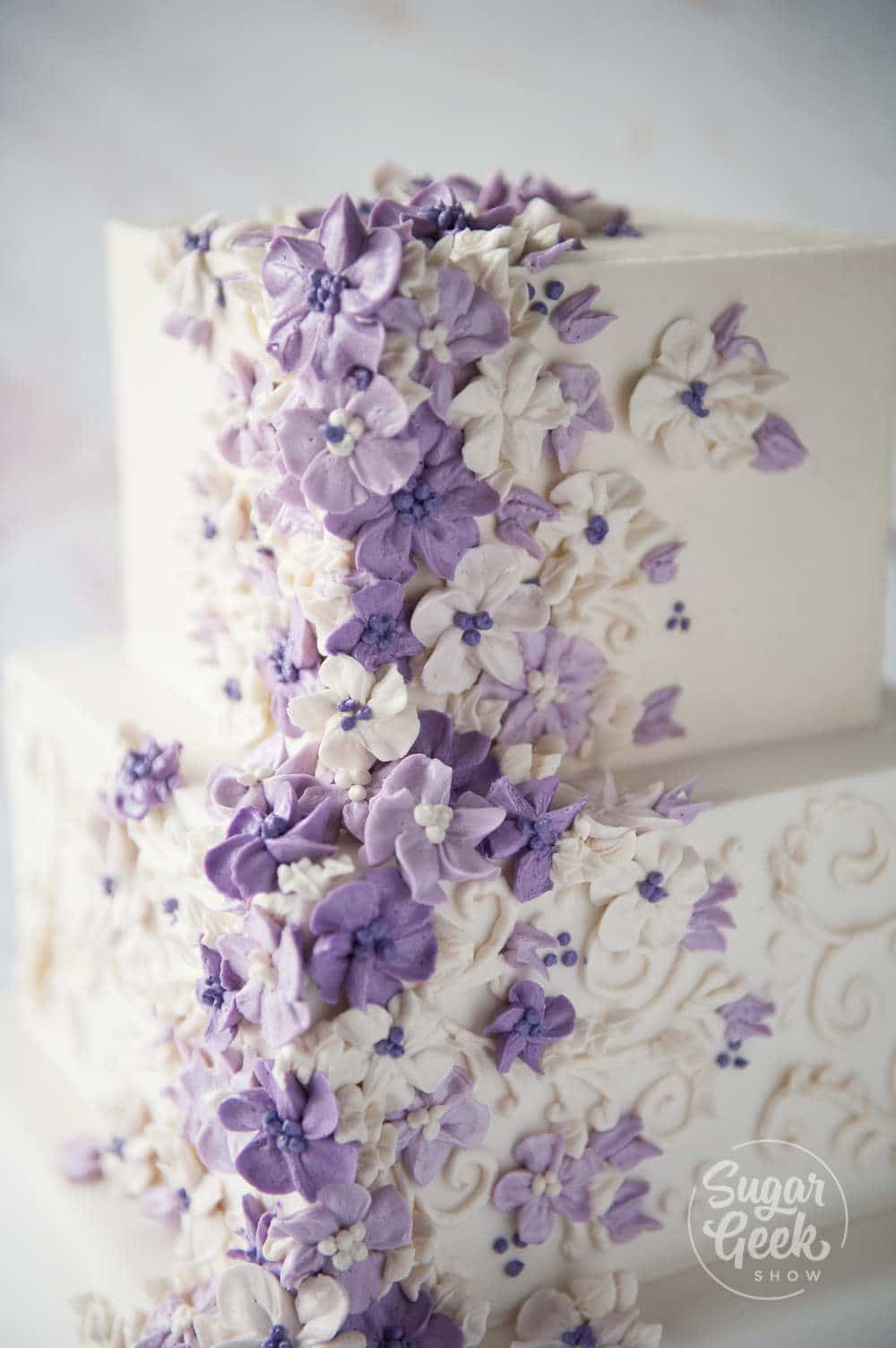 Purple buttercream flowers on a wedding cake