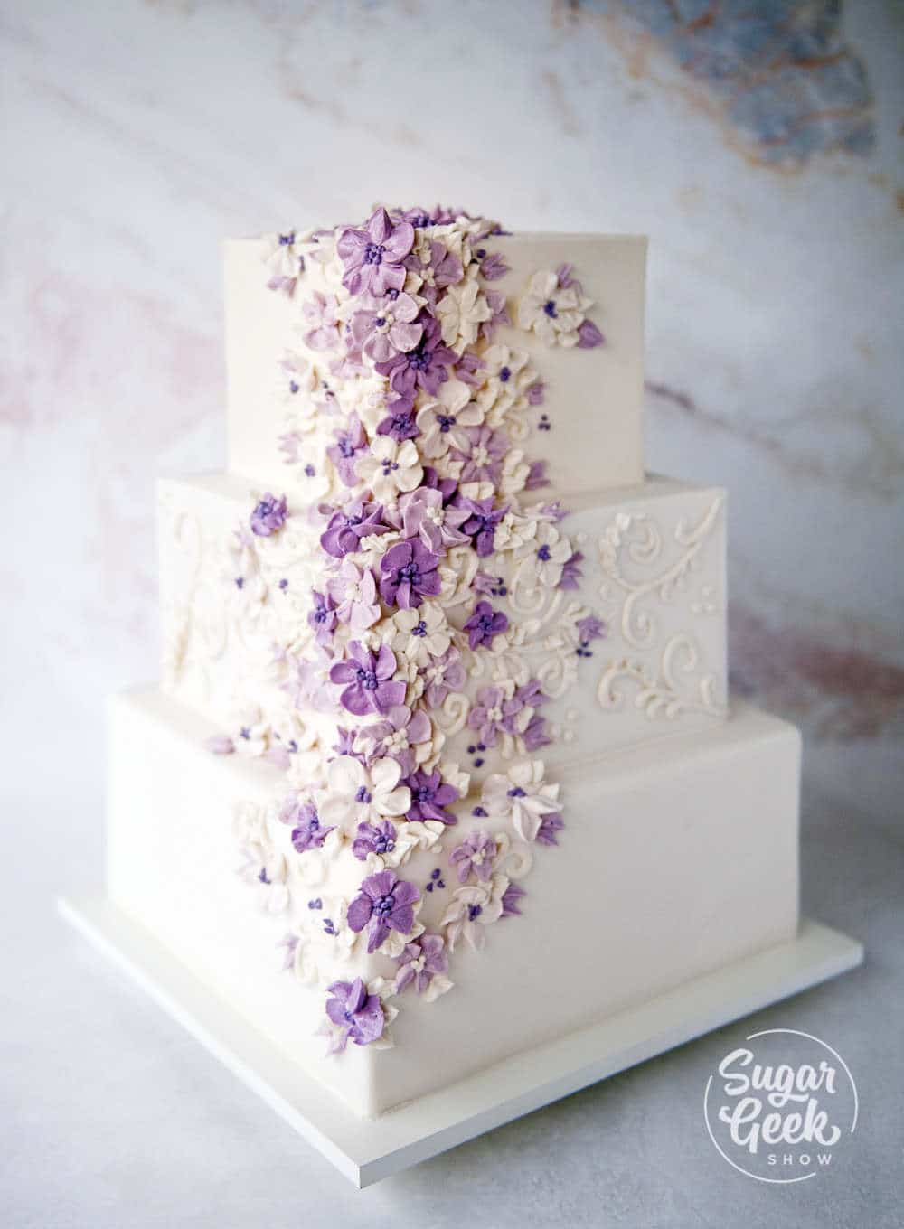 Three tier square white buttercream cake with purple buttercream flowers