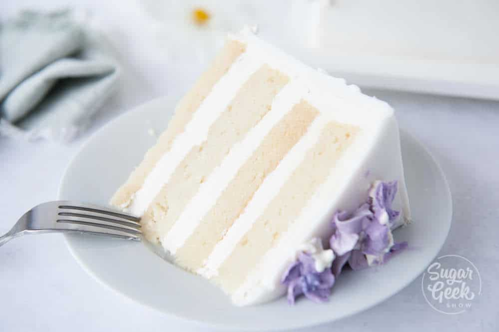 Slice of vanilla cake with buttercream and purple buttercream flowers on a white plate