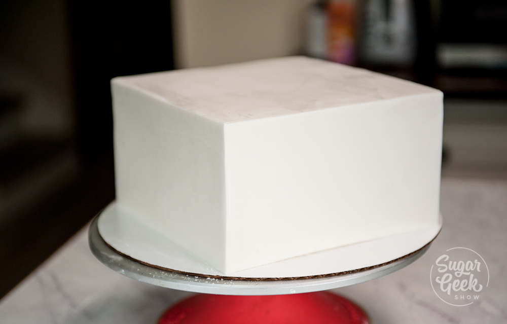 square wedding cake tier covered in fondant sitting on a turntable