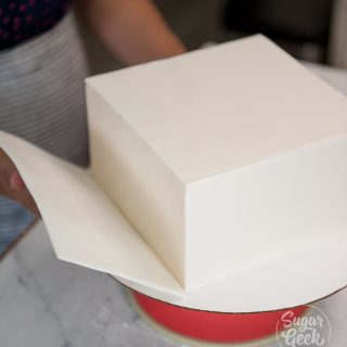 Apply your first square of frozen fondant to the side of your chilled buttercream cake
