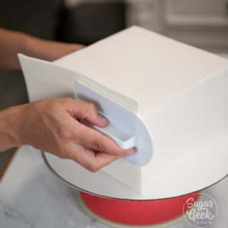 press the fondant against the chilled cake with a fondant smoother and work out any air bubbles. If it's not sticking, spray the cake lightly with water