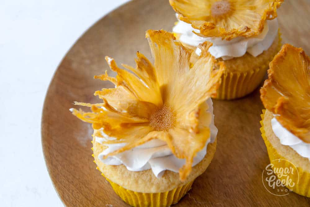 dried pineapple flowers on cupcake on wooden plate