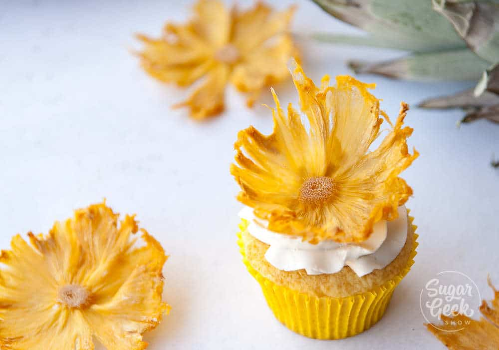 dried pineapple flowers on vanilla cupcake with yellow wrapper and white buttercream frosting