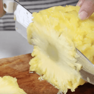 Lay the pineapple on it's side and cut very thin slices with a sharp knife
