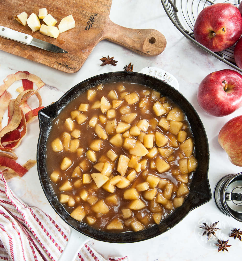top view of apple filling in a cast iron pan surrounded by apples, spices, apple peels and cut up apples