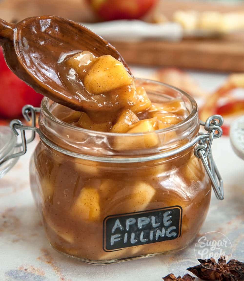 apple filling being spooned into a glass jar with apple filling label