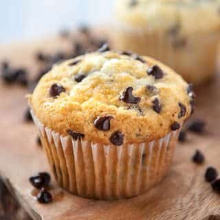 close up of moist chocolate chip muffin on wooden cutting board with blurry chocolate chip muffin in the background and loose chocolate chips all around the muffin