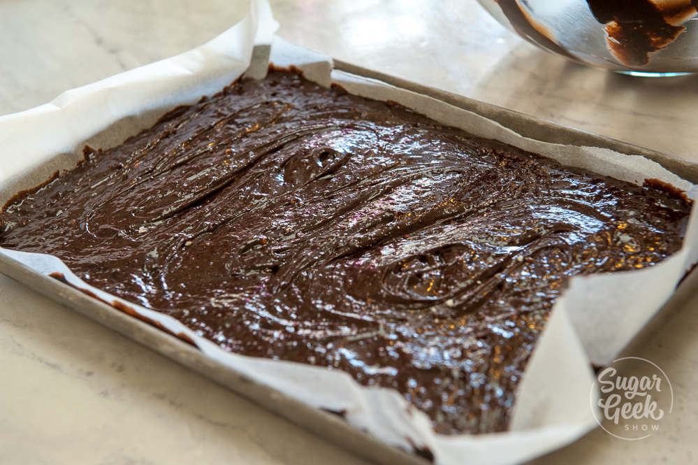 brownie batter in pan lined with parchment paper