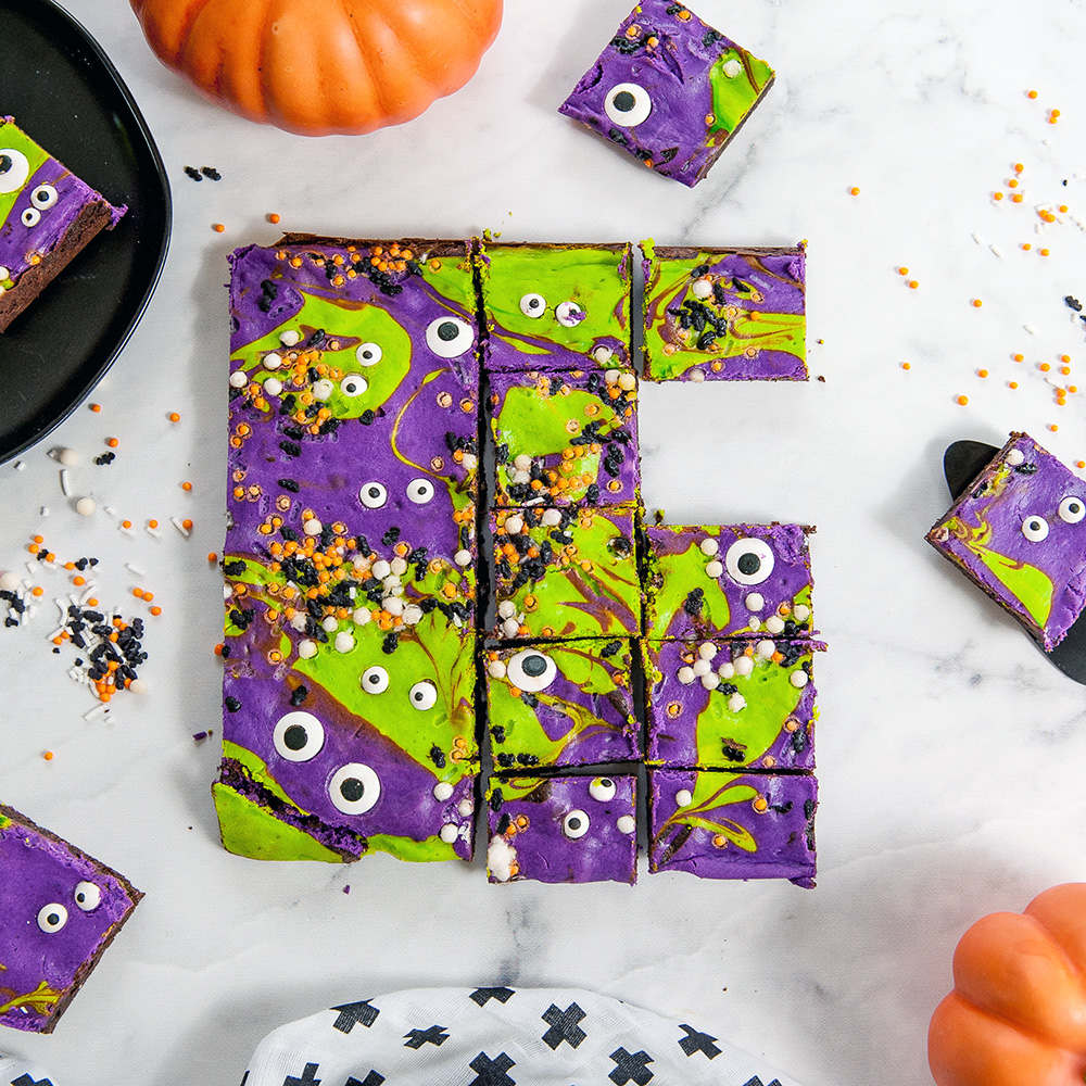 monster mash cheesecake brownies cut into squares on a white background. Sprinkles, pumpkins and plates around the brownies