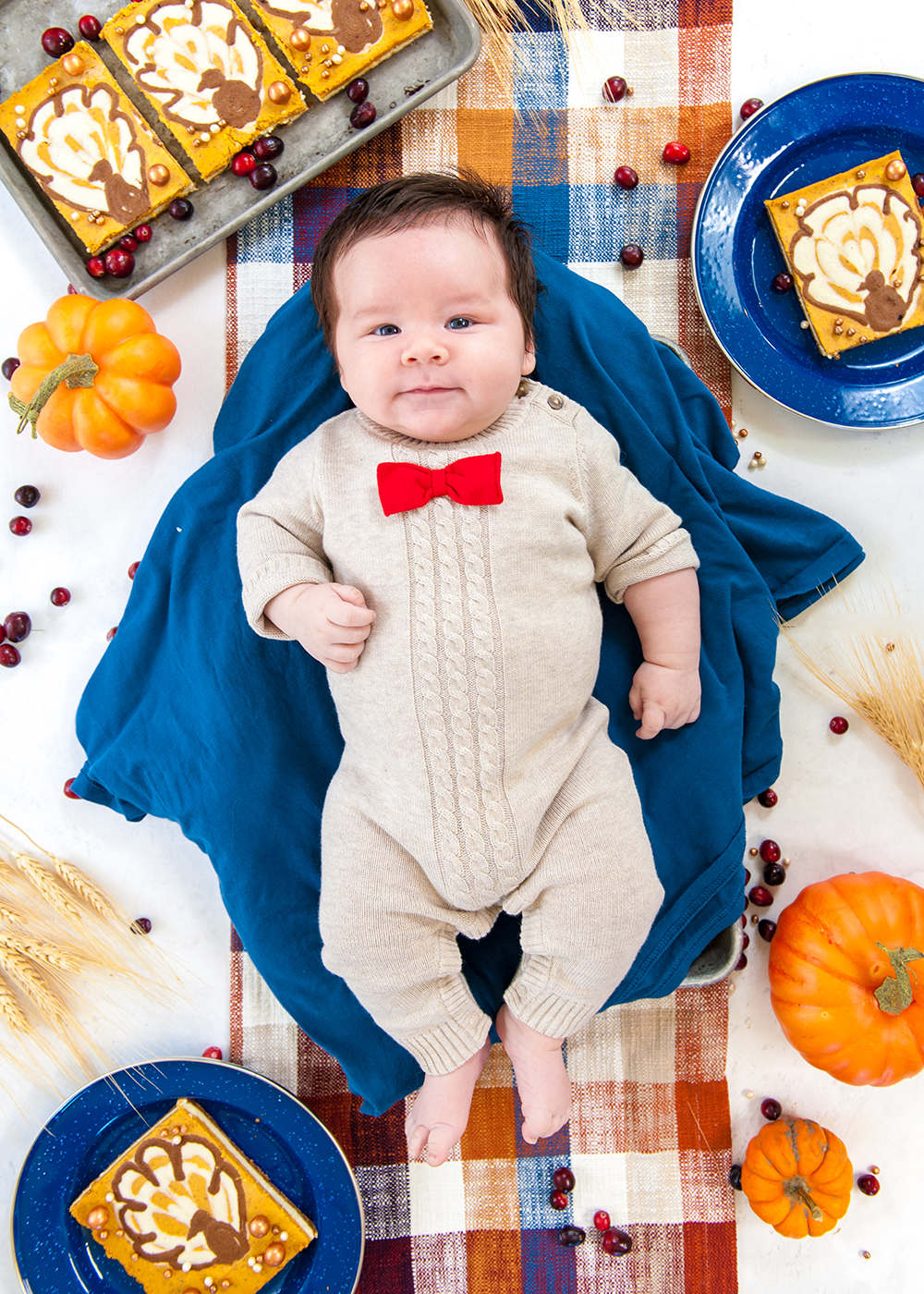 baby boy on blue blanket surrounded by pumpkins and cheesecake bars for monthly growth photo