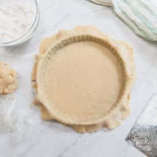 tart dough in tart pan with ingredients around it