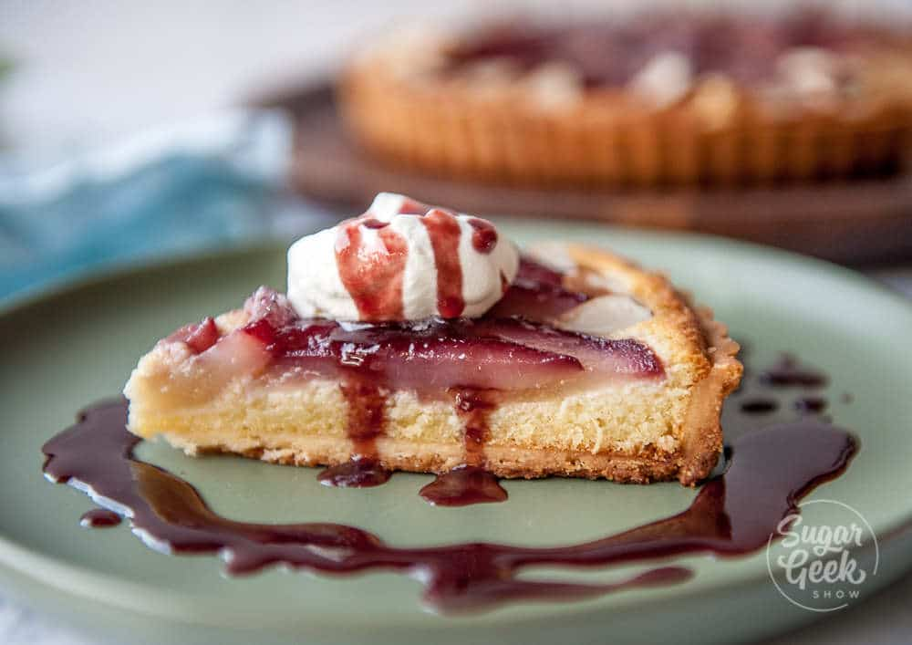 closeup slice of wine poached frangipane tart with whipped cream and drizzle of red wine sauce